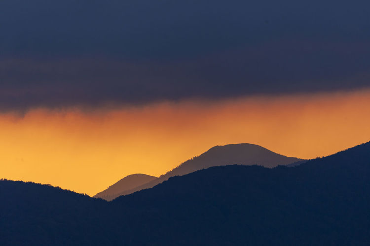 Scenic view of silhouette mountain against romantic sky at sunset
