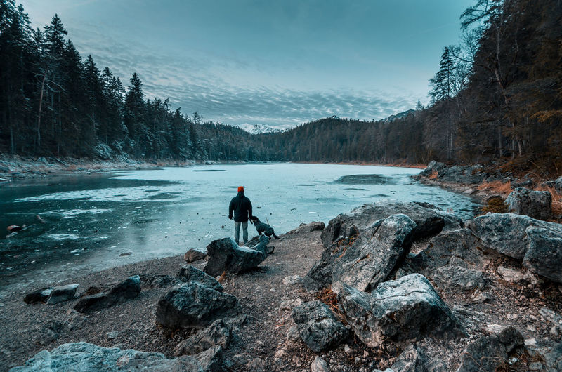 Rear View Of Man With Dog Standing By River In Forest