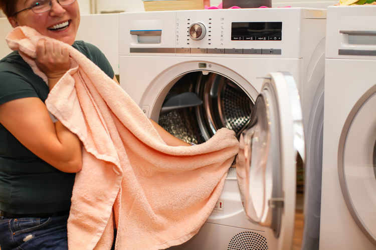 Midsection of happy woman holding towel by washing machine