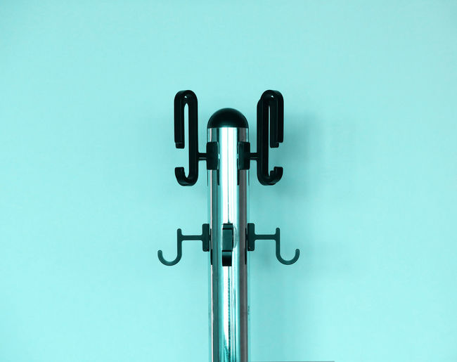 Close-up of hook stand against blue wall