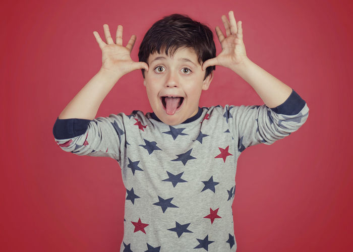 Fun Funny Happy Joke Mockery Arms Raised Boy Child Childhood Colored Background Emotion Expression Face Facial Expression Innocence Kid Language Looking At Camera Making A Face People Portrait Standing