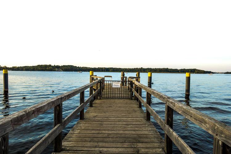 Pier Over Calm Sea Against Clear Sky