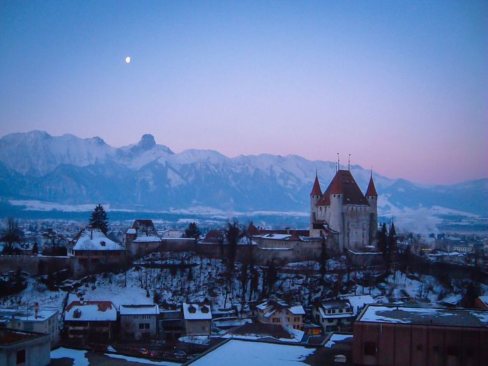 Historic castle in city against swiss alps in winter against clear sky