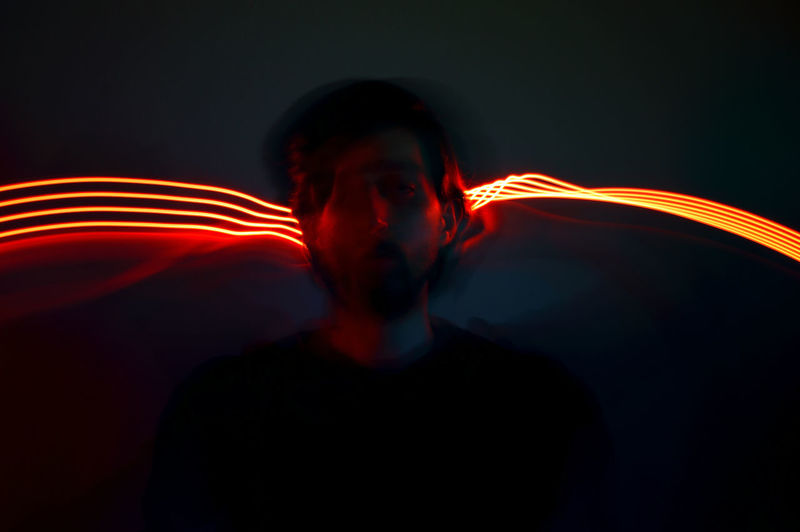 Portrait of light trails against black background