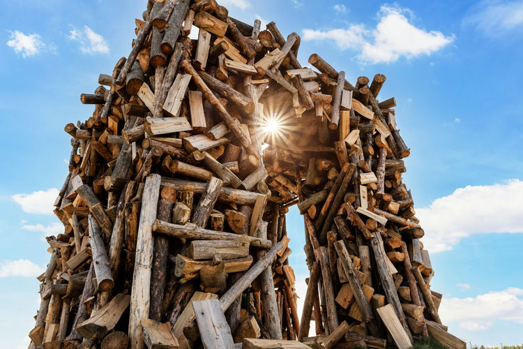 Low angle view of stack of logs on field against sky