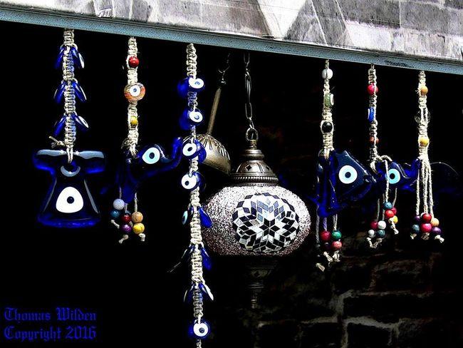 """Man sagt allgemein, dass im Orient Schwarze Magie, Verwünschungen und Flüche (türkisch: Büyü) noch wirkliche Wirkung haben. Diese ' bösen Zaubereien und Flüche' sind in der Türkei auch tatsaechlich gesetzlich verboten und werden bestraft, wenn man angezeigt wird. Nazar-Amulette sind in einigen orientalischen Ländern verbreitete blaue, augenförmige Amulette, die gemäß dem Volksglauben den Bösen Blick abwenden sollen. Der Begriff kommt ursprünglich vom arabischen Ausdruck Nazar / نظر / Naẓar, was u. a. für Sehen, Blick, Einsicht steht. Im Türkischen bezeichnet nazar boncuğu das Nazar-Amulett bzw. wörtlich die Blick-Perle, ebenfalls gebraucht werden die Begriffe mavi boncuk (Blaue Perle), oder göz boncuğu (Augen-Perle). Im Volksglauben besitzen Menschen mit hellblauen Augen den unheilvollen Blick. Ein ebenfalls """"Blaues Auge"""" soll demnach als Gegenzauber diesen Blick bannen und abwenden. Gern werden Nazar-Perlen gegen den Bösen Blick kleinen Kindern an der Kleidung befestigt, hängen als Amulett allgegenwärtig am Innenrückspiegel von vielen Taxen und Lastwagen oder dienen als Verzierung am Schlüsselanhänger. Jedoch findet man sie ebenso an der Eingangstür zu Viehställen. Geht ein """"Auge"""" kaputt, so hat es offensichtlich seinen Dienst getan und einen Bösen Blick abgewendet – und wird schnell durch ein neues ersetzt. Ein Nazar-Amulett wird meistens aus farbigem Glas hergestellt. Es hat oft eine Tropfenform. Kleinere Exemplare sehen eher aus wie Perlen und größere wie flache Scheiben. Das Charakteristische am Nazar-Amulett sind seine Farben: Von innen nach außen konzentrische Kreise ähnlich wie bei der Regenbogenhaut eines Auges in den Farben schwarz oder dunkelblau, hellblau, weiß und dunkelblau. Es wird deshalb auch oft das """"Blaue Auge"""" genannt. Eine andere Bezeichnung ist auch """"Auge der Fatima"""", benannt nach der jüngsten Tochter des Propheten Mohammed. Im Nahen Osten und Nordafrika wird das Abwehrzeichen Hand der Fatima häufig mit einem Nazar kombiniert. Sein Gegenstück –"""