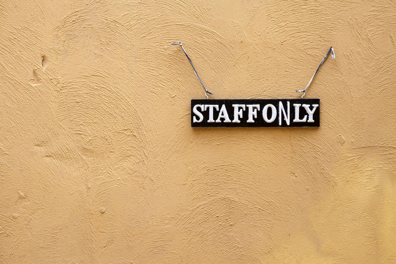 Staff only sign hanging on a brown concrete wall Architecture Backgrounds Building Exterior Built Structure Capital Letter Close-up Communication Day Full Frame Information Message No People Outdoors Pattern Sign Single Word Text Textured  Wall - Building Feature Western Script Yellow