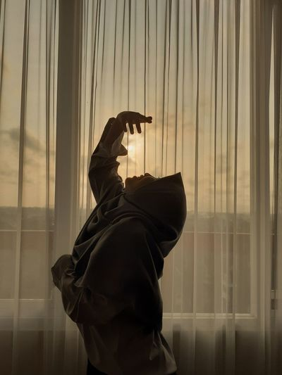 Side view of woman wearing hijab dancing by curtain at home