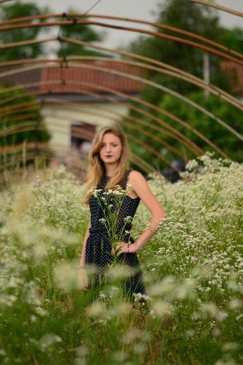 Portrait of young woman standing amidst flowering plants in garden