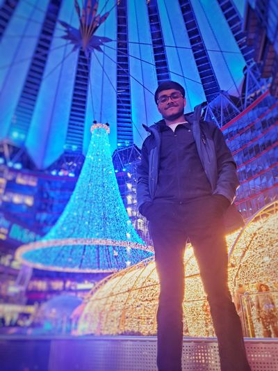 Portrait of young man standing against illuminated buildings in city