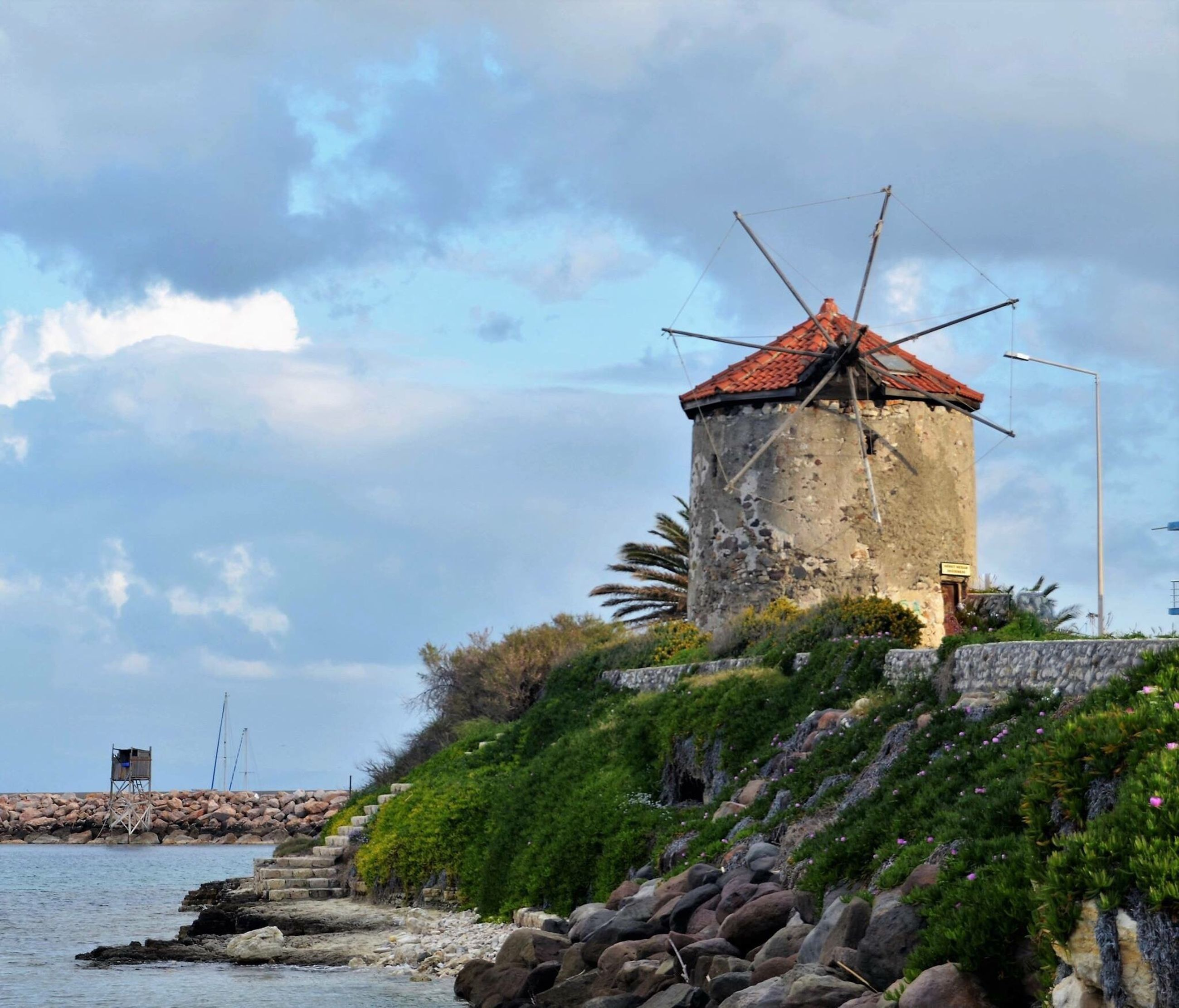 architecture, windmill, water, built structure, nature, building exterior, wind power, sky, environmental conservation, sea, cloud - sky, no people, wind turbine, beauty in nature, outdoors, tree, day, alternative energy