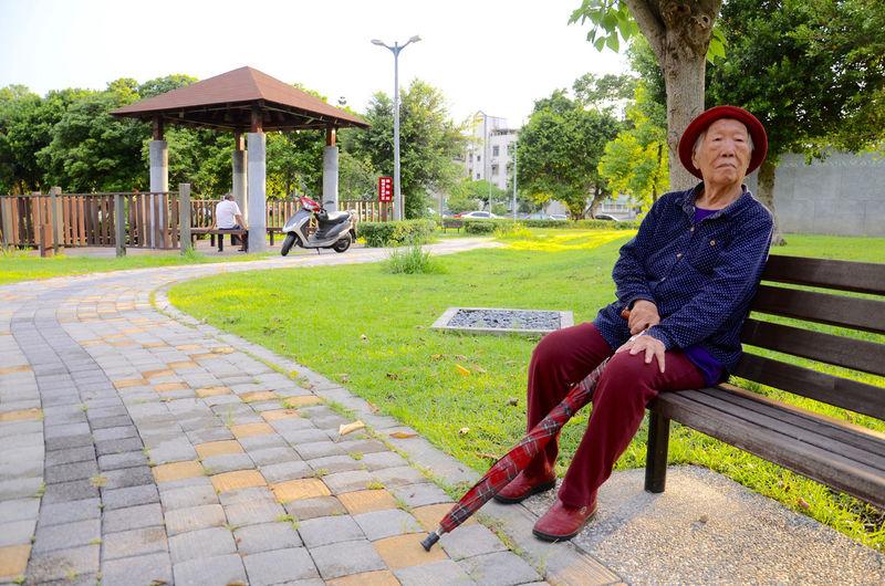 Full length of senior woman relaxing on bench in park