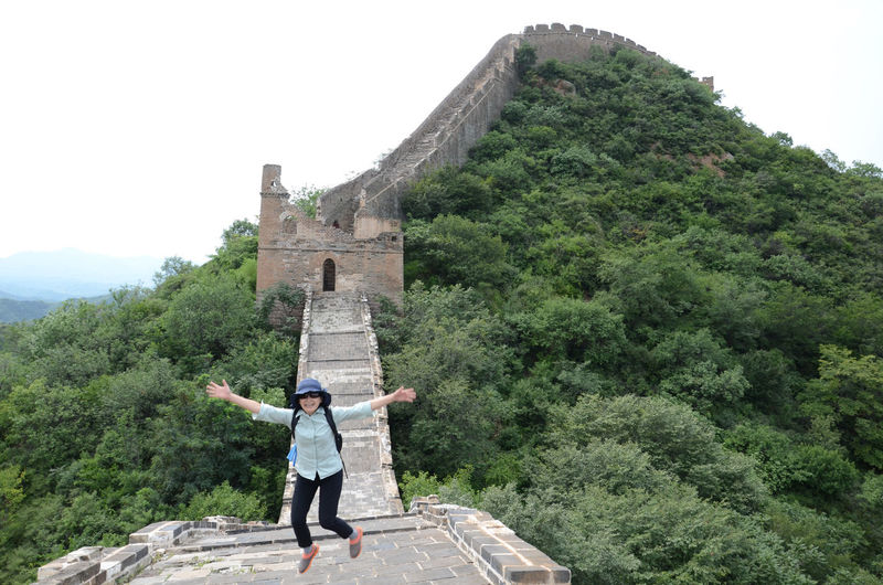 High angle view of woman jumping on great wall of china