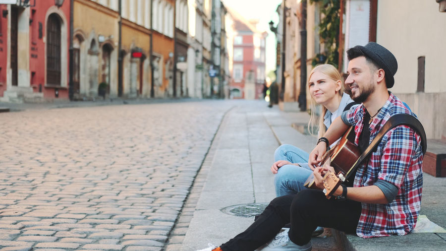 Young couple sitting on street in city