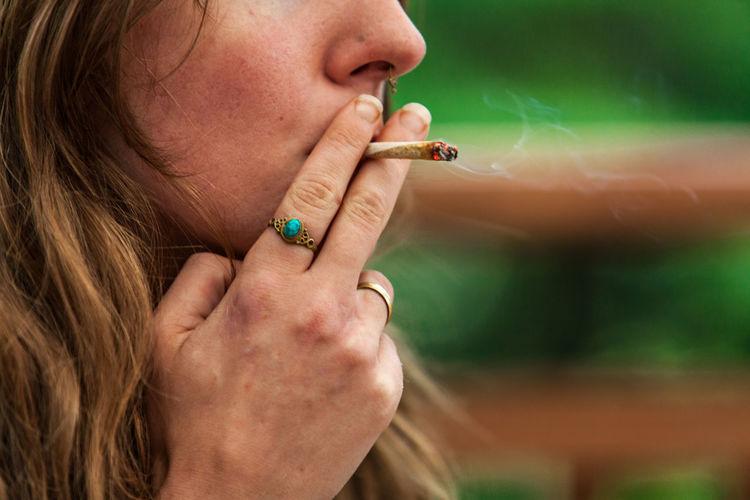 Close-up of woman smoking weed outdoors