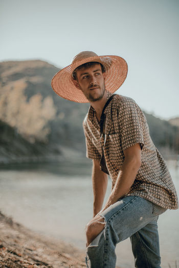 Young man wearing hat standing against lake in forest