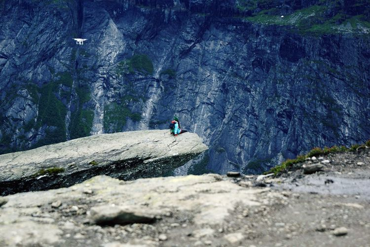 Rear view of woman sitting on cliff