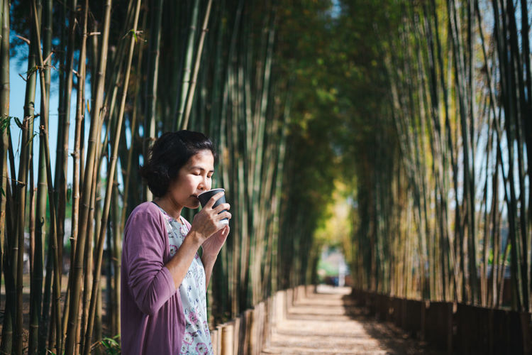 Woman drinking coffee standing at park