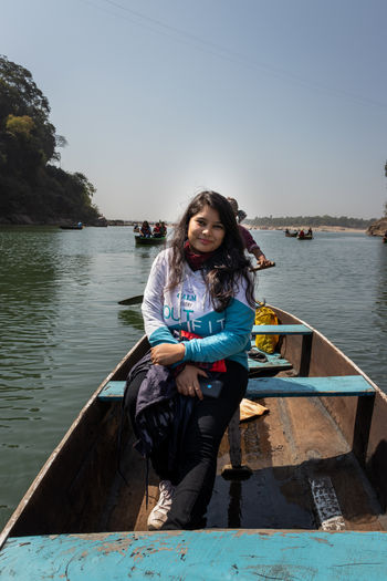 Portrait of young woman sitting on boat in lake against sky