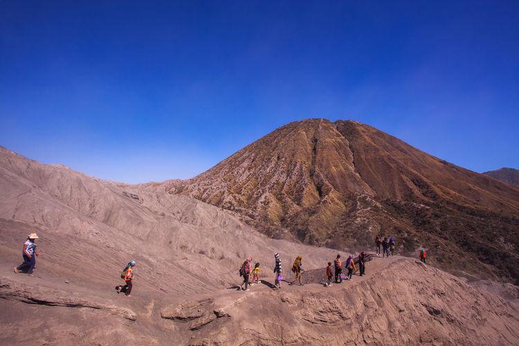 People on desert against clear blue sky