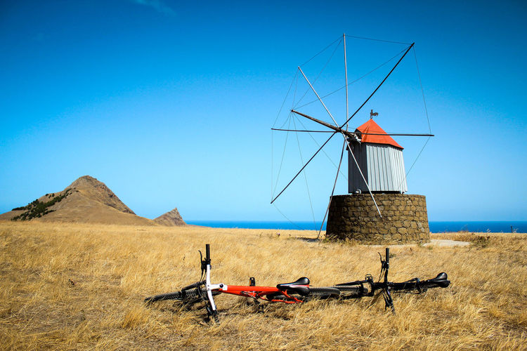 Traditional windmill on field against blue sky during bike trip