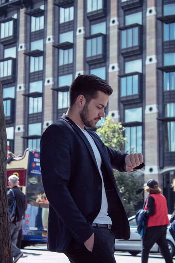 Side View Of Businessman Checking Time While Standing In City