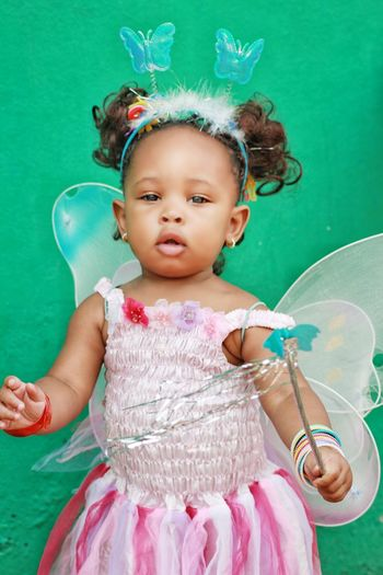 Portrait of cute baby girl wearing fairy costume against wall