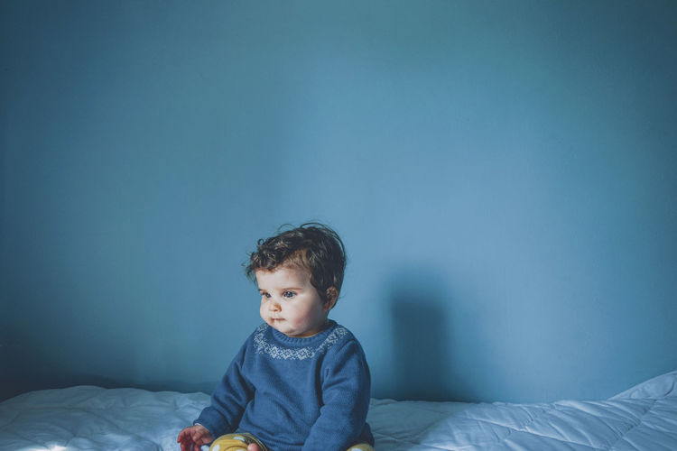 Boy looking away on bed at home