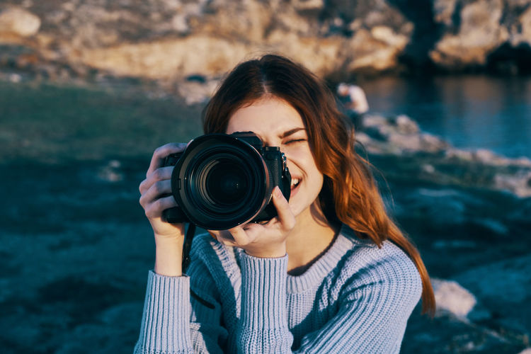 Portrait of young woman photographing