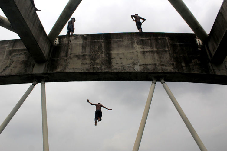 Low Angle View Of Men Jumping From Bridge Against Sky