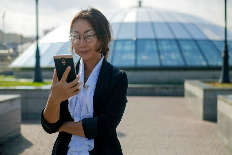 Businesswoman using mobile phone while standing on road against building
