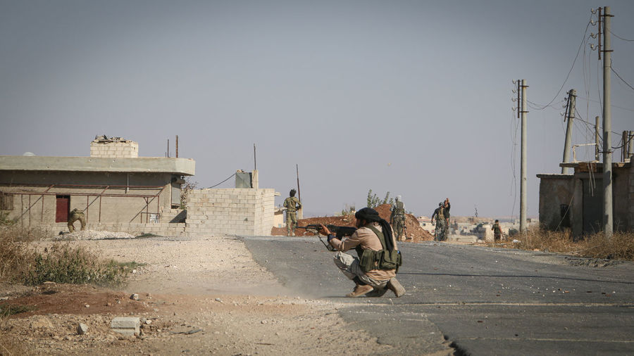 Man aiming gun while crouching on road