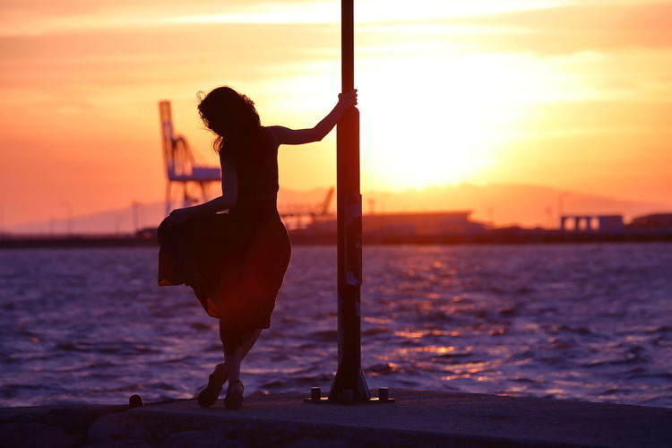 Silhouette woman standing on pier over sea against sky during sunset
