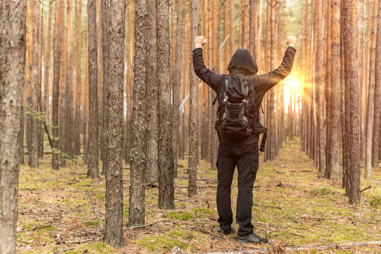 Man in hooded shirt clenching fists against trees
