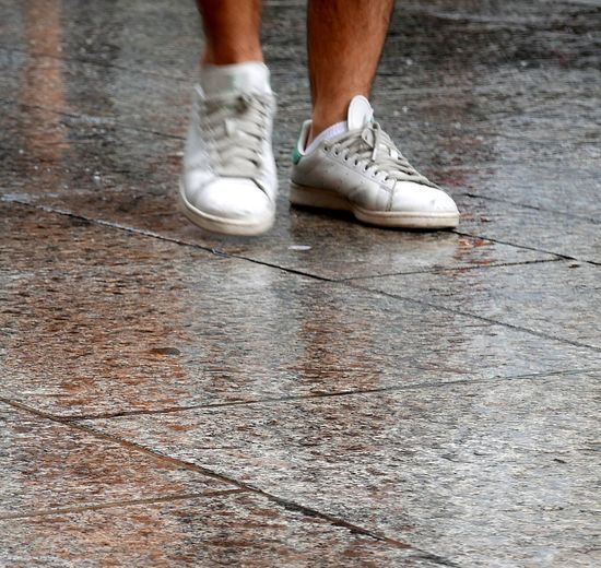 Legs Of Person Walking On Wet Pavement