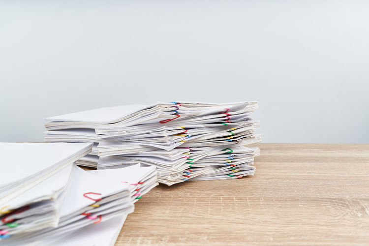 Overload paperwork report of sale and receipt with colorful paper clip on wooden table have blur document on foreground with white background and copy and finance concept success. Business Planning Sale Stack Account Background Business Concept Desk Document Finance Office Overload Paper Paperwork Pile Profit Report Stack Success Tax Wealth White Wooden Workload