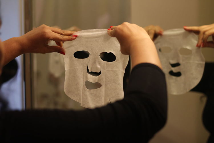 Cropped hands of woman using facial mask at home