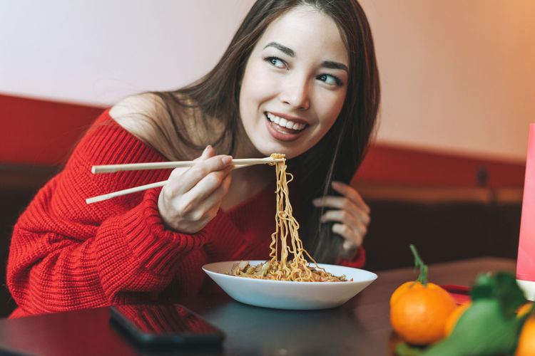 Beautiful asian woman in red clothes eating asian food with chopsticks in chinese restaurant