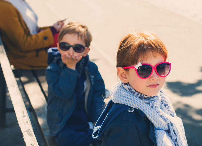 Portrait of siblings wearing sunglasses sitting on bench