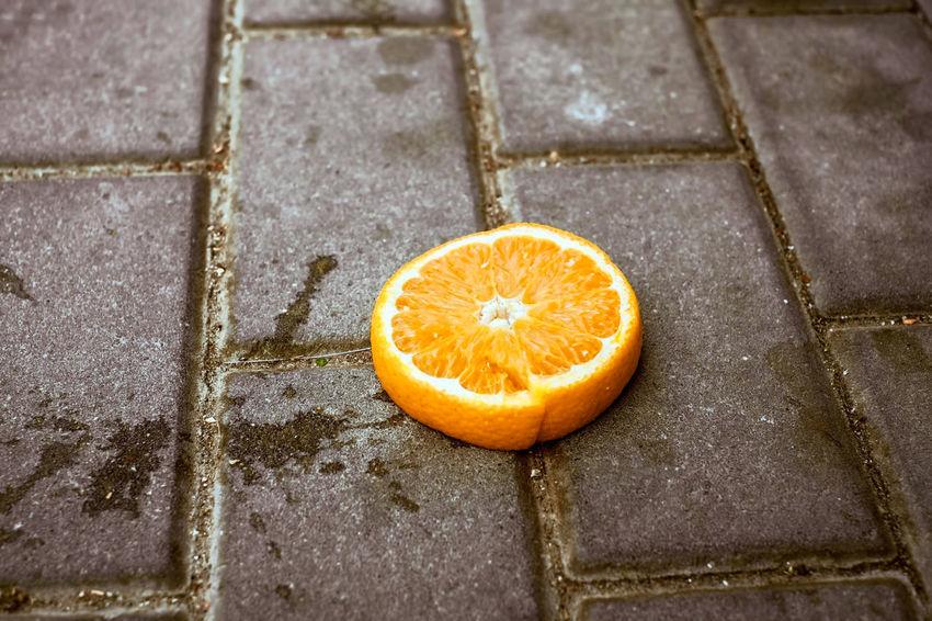 a slice of orange on the sidewalk Orange Sidewalk Citrus Fruit Close-up Day Food Food And Drink Footpath Freshness Fruit Healthy Eating High Angle View No People Orange Orange - Fruit Orange Color Outdoors Pavement Paving Stone Shape Slice Of Orange Stone Wellbeing Yellow EyeEmNewHere