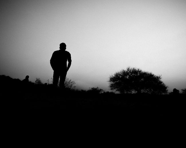 Rear view of silhouette man standing on field against clear sky