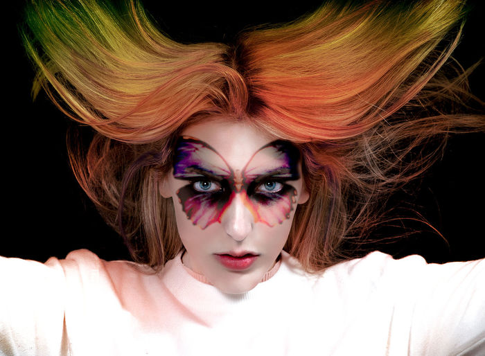Portrait of woman with painted face and dyed hair against black background