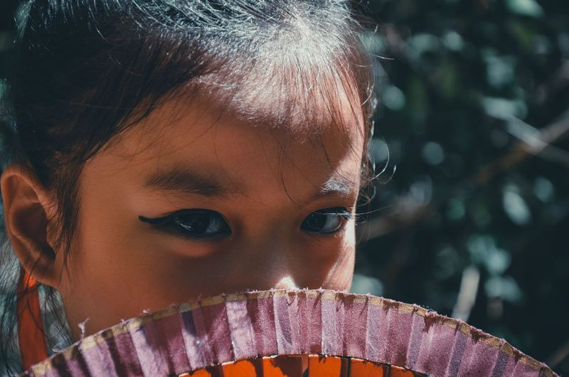 Close-up portrait of cute girl with hand fan