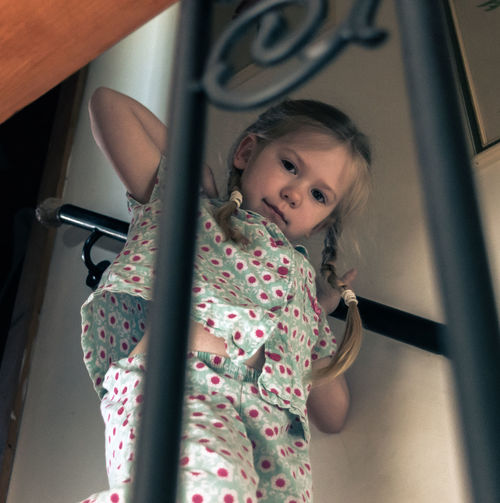Low Angle Portrait Of Girl Wearing Pajamas Standing On Steps At Home