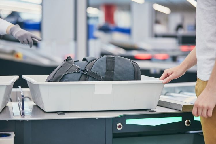 Midsection of man picking suitcase from conveyor belt