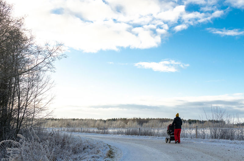 Rear view of person on snow field against sky