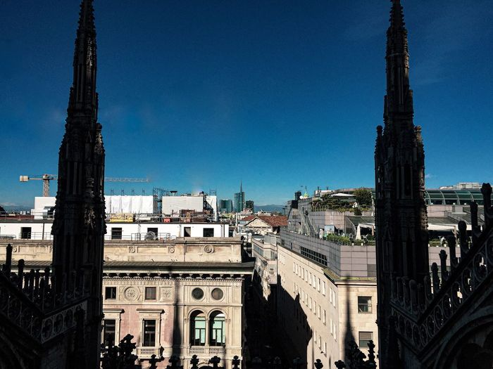 Duomo di milano and buildings in city against clear blue sky