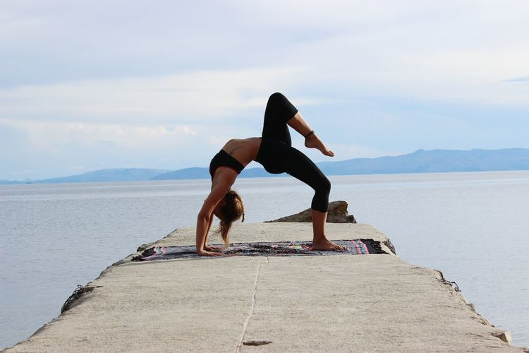 Full length of woman doing yoga on pier amidst sea
