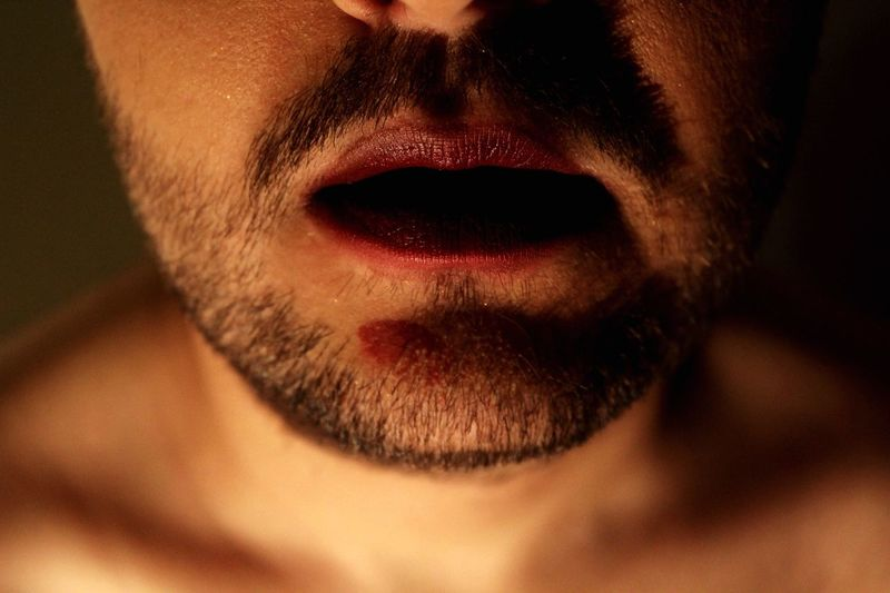 Midsection of man with lipstick and stubble