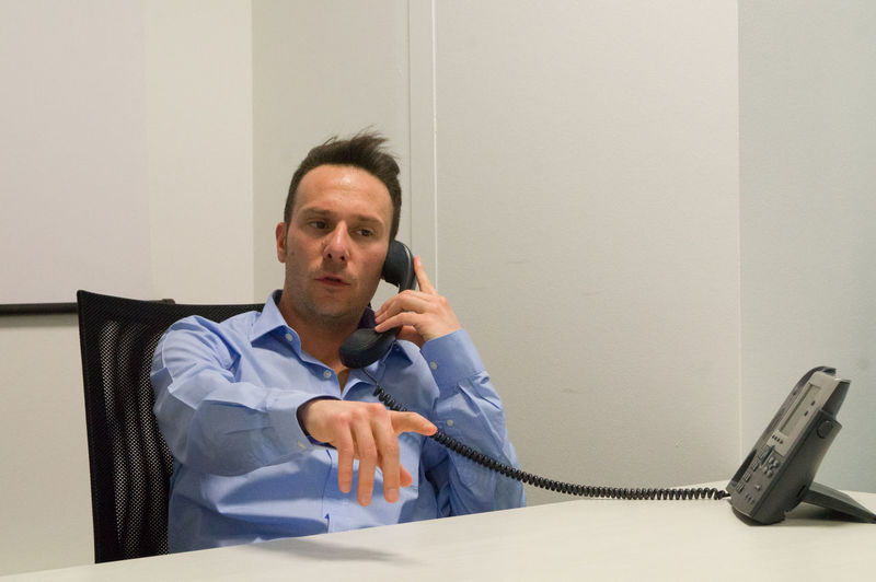 Businessman Talking On Telephone While Sitting At Office